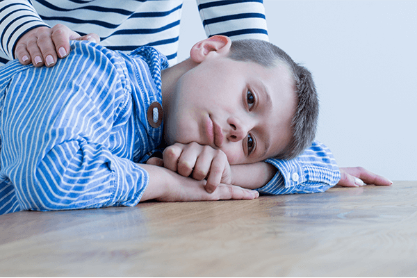ילד אוטיסטי יושב עם הראש מונח על הידיים כדי להמחיש את המצוקה בה נמצאים ילדים אלה ואיך ניתן לשפר את איכות החיים של ילדים אלה.