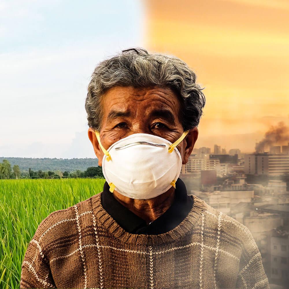 איש עם מסכת פנים וברקע טבע שמחולקת לשתיים: שדה ירוק ובריא מול אזור תעשייה עם אוויר מזוהם