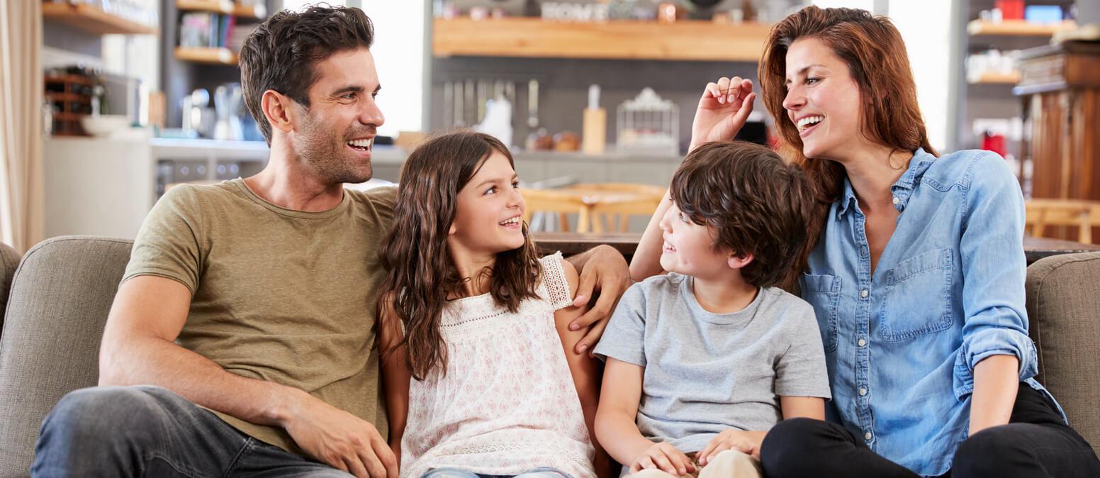משפחה שיושבת על ספה ומבלה ביחד, אחד הדברים שעוזר להגיע לאושר פנימי