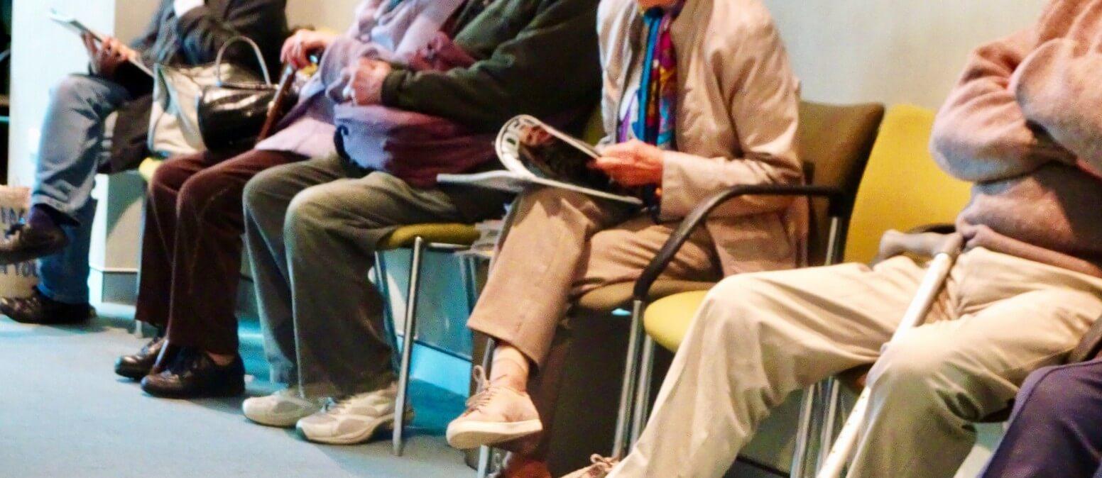 אנשים מבוגרים שממתינים בתור לקופת חולים כסמל למחלות רקע שמגבירות את הסיכוי למות ממחלת הקורונה